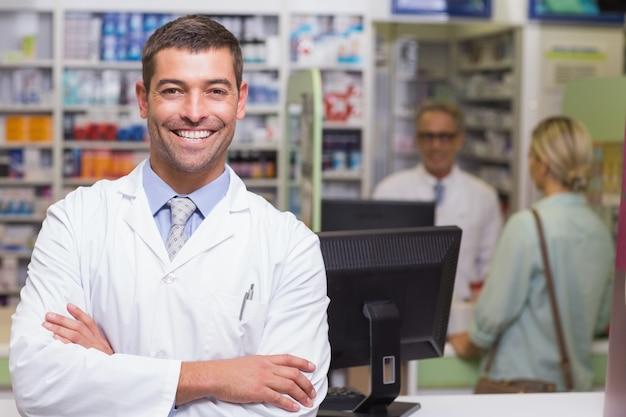 Uśmiechnięta farmaceuta patrzeje kamerę
