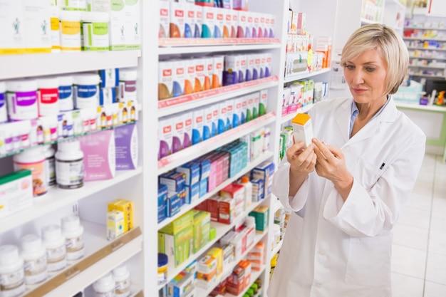 Uśmiechnięta farmaceuta patrzeje medycynę