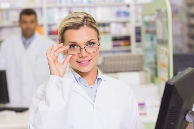 Uśmiechnięta farmaceuta używa komputer
