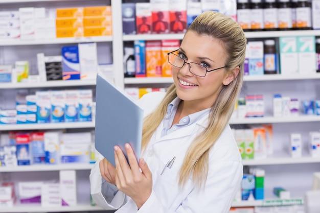 Uśmiechnięta farmaceuta używa pastylka komputer osobistego
