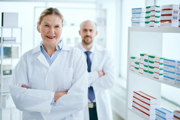 Uśmiechnięta farmaceutka stojąca w swojej aptece