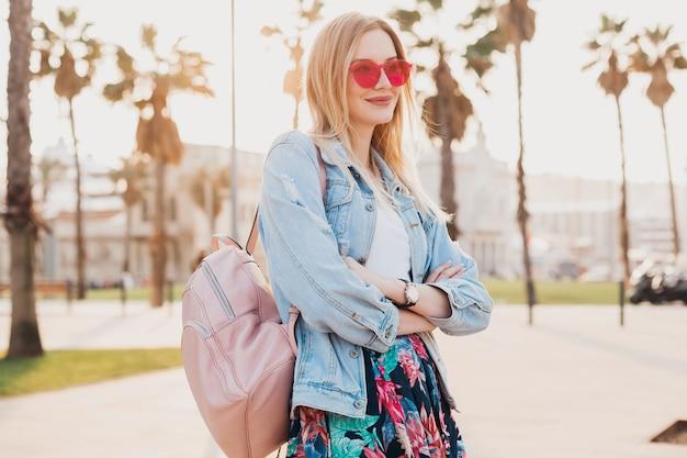 Uśmiechnięta flirtująca kobieta spacerująca po ulicy w stylowej drukowanej spódnicy i dżinsowej kurtce oversize w różowych okularach przeciwsłonecznych
