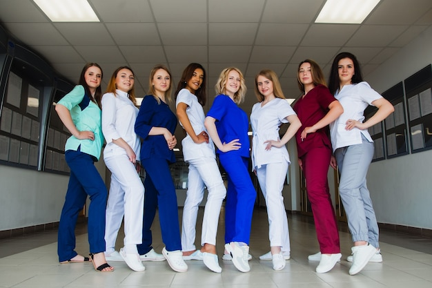 Uśmiechnięta grupa młodych studentów medycyny z mieszaną rasą na uniwersytecie. kadra profesjonalnych pielęgniarek. zaawansowana szkoła szkoleniowa
