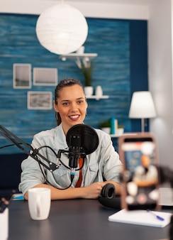 Uśmiechnięta gwiazda mediów społecznościowych siedzi przed kamerą i kręci wideo na kanał youtube. vlogger mówiący i nagrywający online talk show w domowym studiu przy użyciu nowoczesnego sprzętu do cyfrowego podcastu.