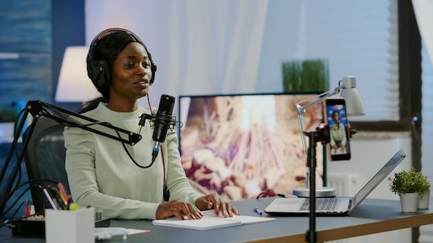 Uśmiechnięta gwiazda mediów społecznościowych siedzi przed kamerą machając i kręcąc wideo na kanał youtube za pomocą smartfona. vlogger mówiący i nagrywający online talk show w domowym studio do cyfrowego podcastu