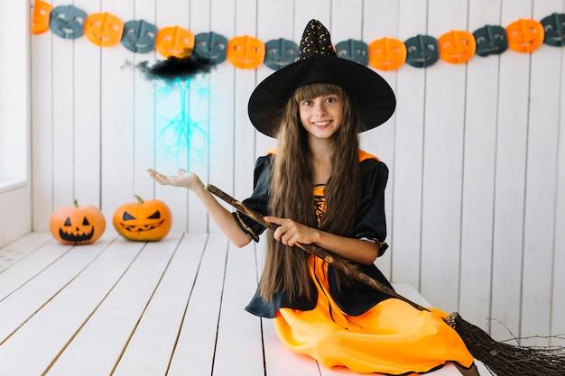 Uśmiechnięta halloweenowa czarownica robi magii