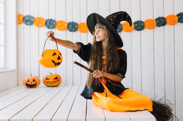 Uśmiechnięta halloweenowa czarownica trzyma jack-o-lantern