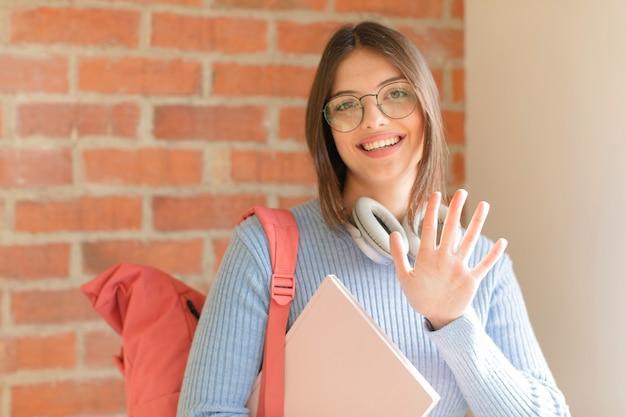 Uśmiechnięta i kobieta wyglądająca przyjaźnie, pokazująca cyfrę piątą lub piątą z ręką do przodu, odliczającą