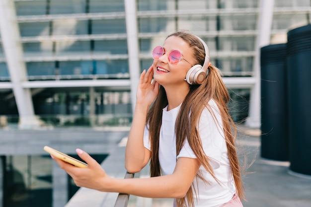 Uśmiechnięta i tańcząca młoda kobieta trzyma smartfon i słucha muzyki w słuchawkach