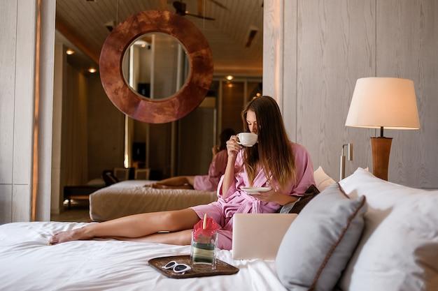 Uśmiechnięta idealna kobieta w różowym szlafroku z filiżanką herbaty / kawy i laptopa siedzącego łóżka w przytulnym pokoju hotelowym.