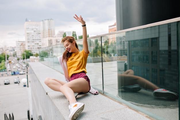 Uśmiechnięta imbirowa dziewczyna w żółtej koszuli, leżąc na kamiennym parapecie i patrząc w dół
