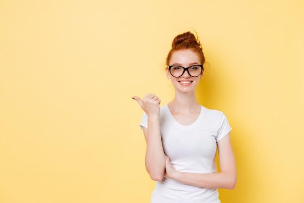 Uśmiechnięta imbirowa dziewczyna wskazuje daleko od w eyeglasses