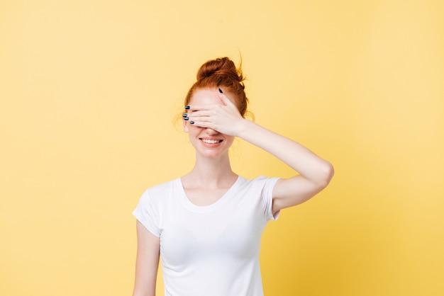 Uśmiechnięta imbirowa kobieta w koszulce zakrywa jej twarz