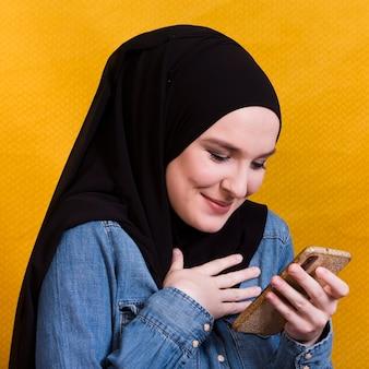 Uśmiechnięta islamska kobieta patrzeje jej telefon z chustka na głowę