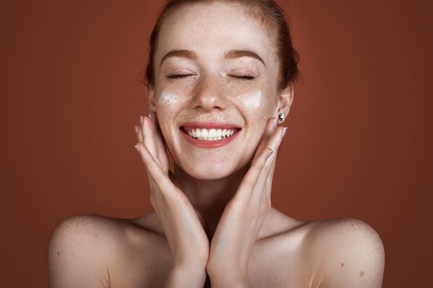 Uśmiechnięta kaukaska imbirowa dama z piegami nakładająca krem przeciw starzeniu na twarz i uśmiech pozująca z nagimi ramionami na czerwonej ścianie