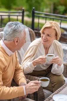 Uśmiechnięta kaukaska kobieta rozmawia z mężem na zewnątrz