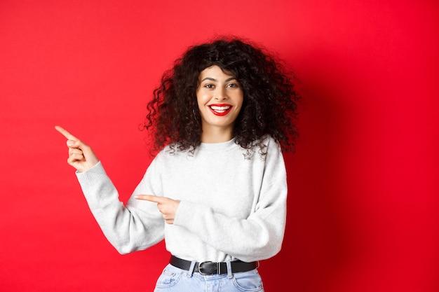 Uśmiechnięta Kaukaska Kobieta Z Kręconymi Włosami I Czerwonymi Ustami, Wskazująca Palcem W Lewo, Pokazująca Ofertę Promocyjną, Stojąca Przy ścianie Studia Premium Zdjęcia