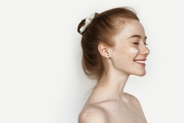 Uśmiechnięta kaukaska kobieta z rudymi włosami i piegami pozuje z kremem pod oczami i nagim ramieniem na białej ścianie studia z wolną przestrzenią