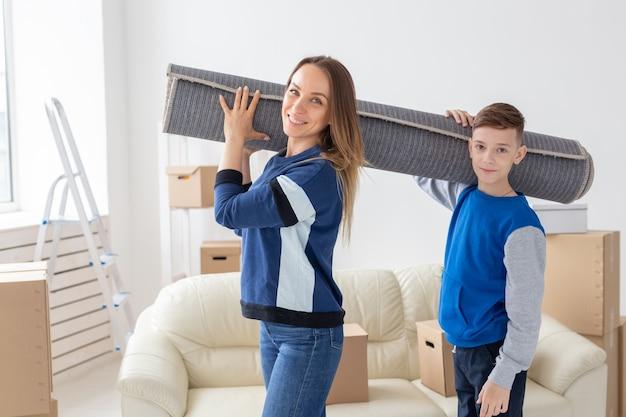 Uśmiechnięta kaukaska matka i uroczy syn trzymają na ramionach złożony dywan