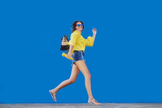 Uśmiechnięta kaukaska nastoletnia dziewczyna trzyma sok pomarańczowego w żółtej bluzce i okularach przeciwsłonecznych podczas gdy biegający przed błękit ścianą.