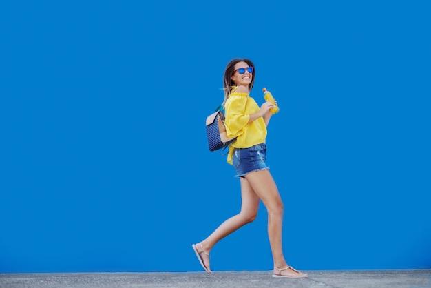Uśmiechnięta kaukaska nastoletnia dziewczyna trzyma sok pomarańczowego w żółtej bluzce i okularach przeciwsłonecznych podczas gdy biegający przed błękitnym tłem.