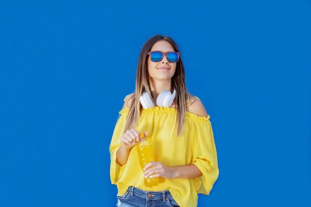 Uśmiechnięta kaukaska nastoletnia dziewczyna trzyma sok pomarańczowego w żółtej bluzce i okularach przeciwsłonecznych podczas gdy stojący przed błękit ścianą.