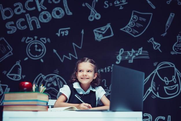 Uśmiechnięta kaukaska uczennica siedząca przy laptopie podczas lekcji online nauki na odległość w szkole
