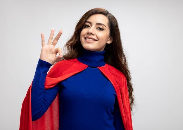 Uśmiechnięta kaukaski dziewczyna superbohatera z czerwoną peleryną gestami ok ręką znak na białym tle