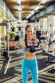 Uśmiechnięta kaukaski kobieta pasuje z kucykiem i ubrana w sportową podnoszenia kettlebell stojąc w siłowni.