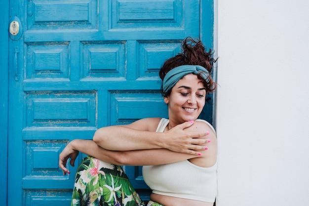 Uśmiechnięta kaukaski kobieta siedzi przed niebieskimi drzwiami w okresie letnim. styl życia na zewnątrz