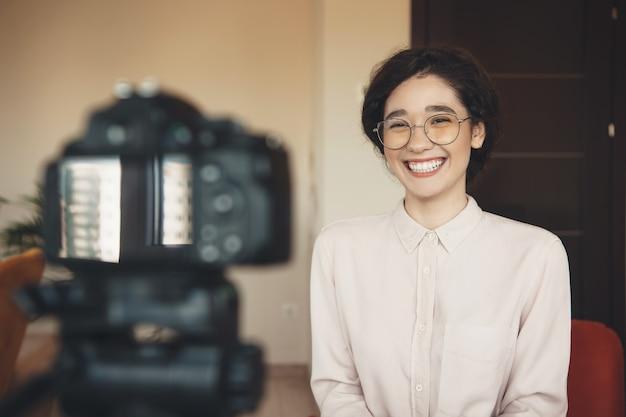 Uśmiechnięta kaukaski kobieta w okularach na sobie wizytowy ma konferencję online przy użyciu aparatu fotograficznego