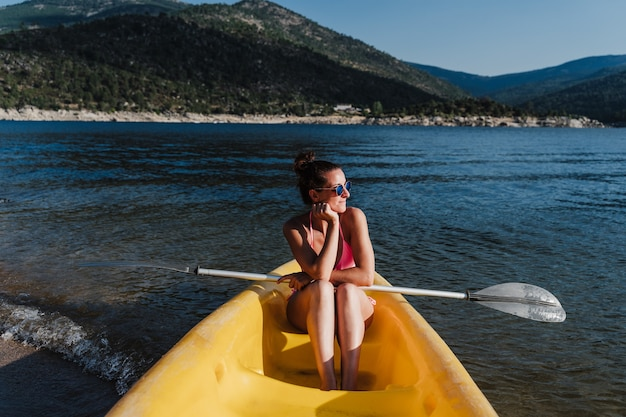 Uśmiechnięta kaukaski kobieta w pływać nosić trzymając wiosło siedząc na żółtym kajaku w jeziorze w słoneczny dzień. czas letni. sport, przygoda i przyroda