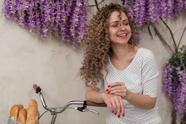 Uśmiechnięta kędzierzawa dziewczyna opierał na jej bicyklu z koszem