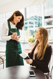 Uśmiechnięta kelnerka bierze rozkaz w kawiarni