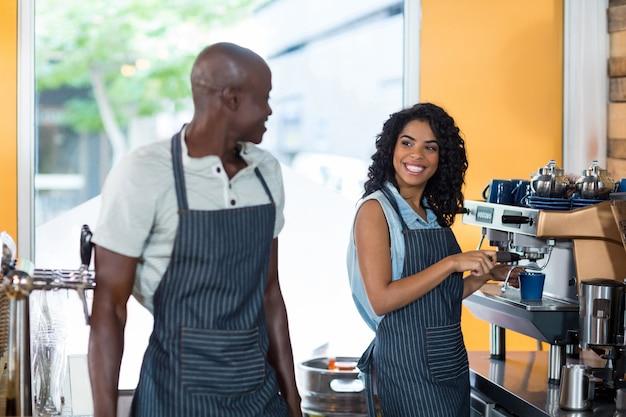 Uśmiechnięta kelnerka i kelner interakcji podczas pracy w kasie