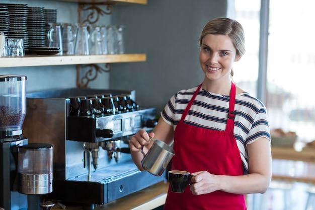 Uśmiechnięta kelnerka robi filiżance kawy przy kontuarem w kawiarni