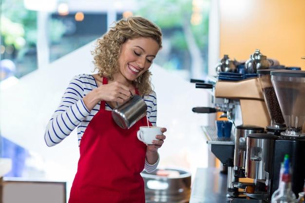 Uśmiechnięta kelnerka robi filiżance kawy przy kontuarem
