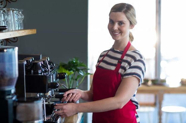 Uśmiechnięta kelnerka robi filiżance kawy w sklep z kawą