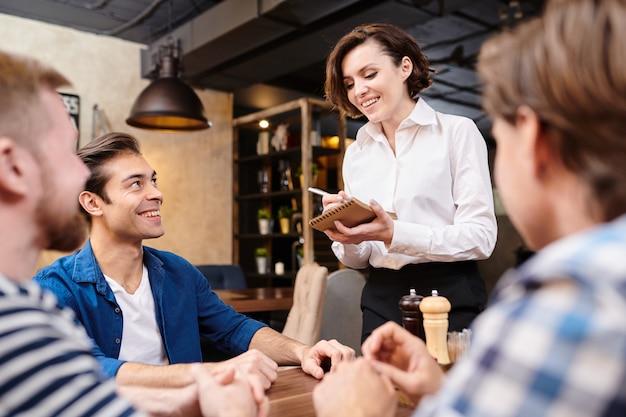 Uśmiechnięta kelnerka robi notatki podczas przyjmowania zamówienia