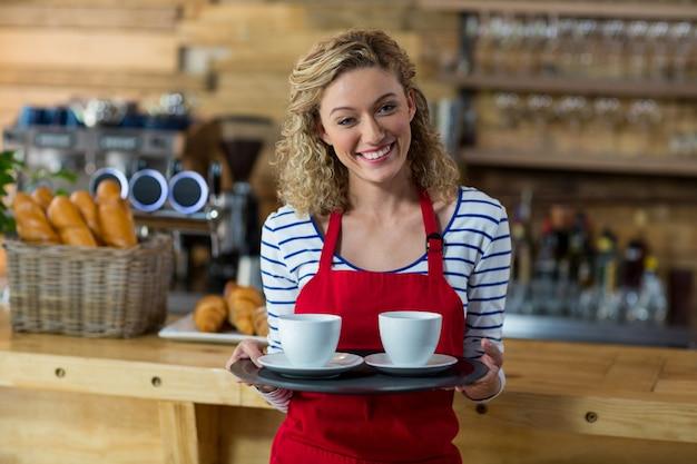 Uśmiechnięta kelnerka stojąca przy filiżance kawy