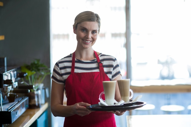 Uśmiechnięta kelnerka trzyma filiżankę zimna kawa przy kontuarem w kawiarni