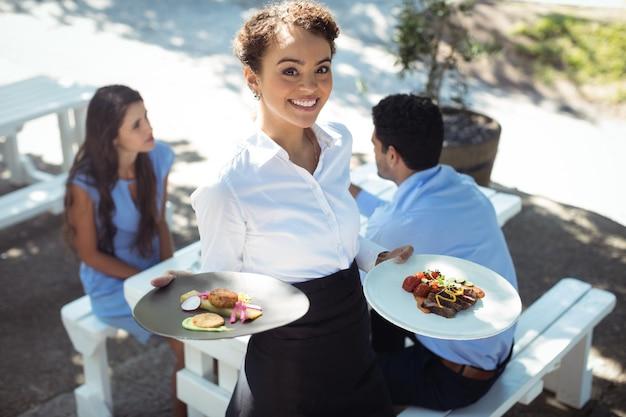 Uśmiechnięta kelnerka trzyma pyszne jedzenie w kuchni