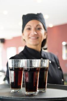 Uśmiechnięta kelnerka trzyma szkła alkoholiczni napoje