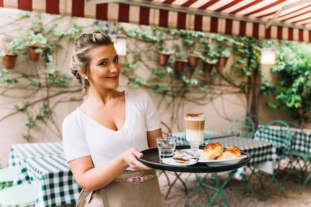 Uśmiechnięta kelnerka trzyma tacę
