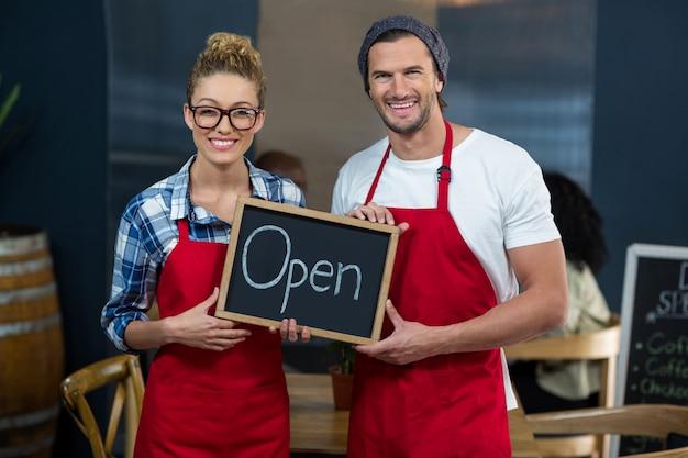 Uśmiechnięta kelnerki i kelnera pozycja z otwartym znakiem wsiada w kawie