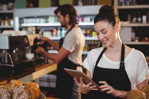 Uśmiechnięta kelnerki pozycja przy kontuarem używać cyfrową pastylkę
