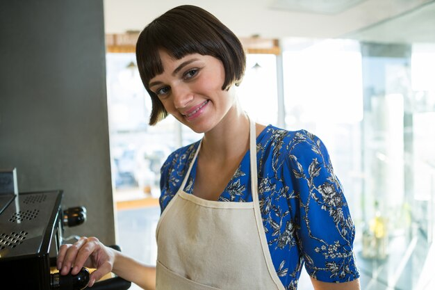 Uśmiechnięta kelnerki pozycja w sklep z kawą