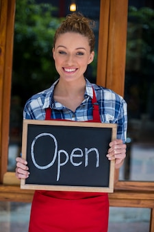 Uśmiechnięta kelnerki pozycja z otwartą znak deską na zewnątrz kawy