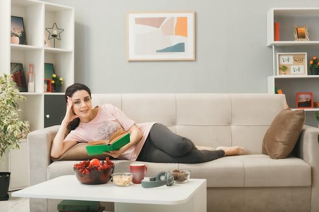 Uśmiechnięta, kładąca dłoń na głowie młoda dziewczyna leżąca na kanapie za stolikiem kawowym, trzymająca książkę w salonie