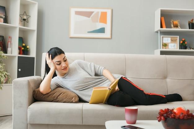 Uśmiechnięta kładąca dłoń na policzku młoda dziewczyna czytająca książkę leżącą na kanapie za stolikiem kawowym w salonie
